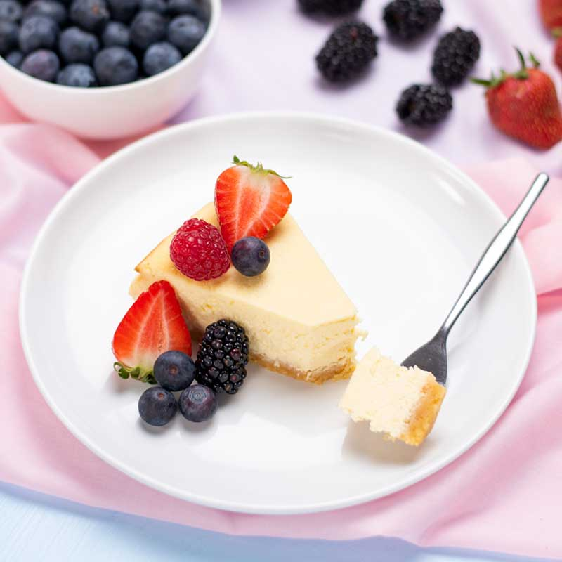 A slice of Keto Baked Vanilla Cheesecake topped with berries on a plate.