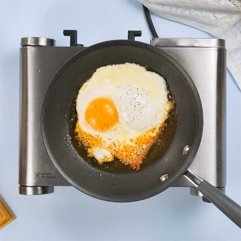 Keto Fried Eggs with Cheese cooking in a frying pan.