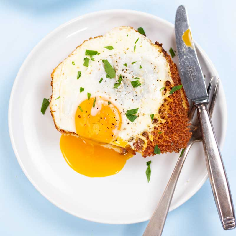 Keto Fried Eggs with Cheese on a plate with a slice removed and yolk pouring out.