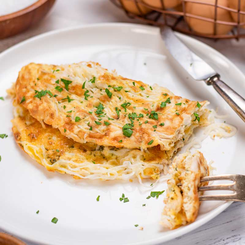 A Keto Chicken Noodle Omelette on a white plate with a slice cut from one end.