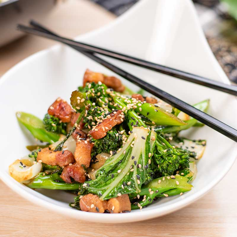 Keto Pork Belly Stir Fry in a white bowl with black chopsticks.