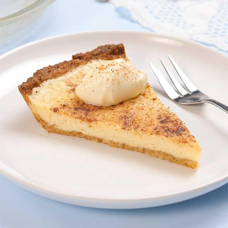 A slice of Keto Sugar Cream Pie with a dollop of cream on top