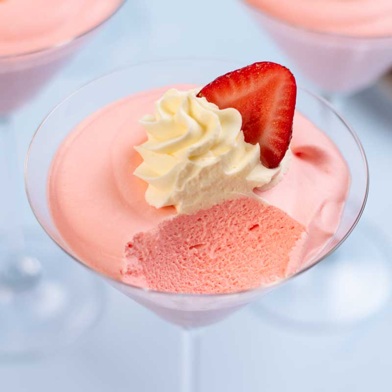 Keto Strawberry Whipped Jello in a martini glass topped with whipped cream and a slice of strawberry with a spoonful removed to show the fluffy insides.
