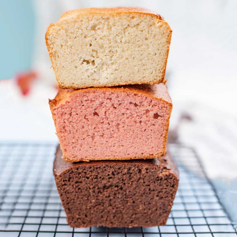 Loaves of Chocolate, Strawberry, and Vanilla Keto Ice Cream Bread stacked on top of each other.
