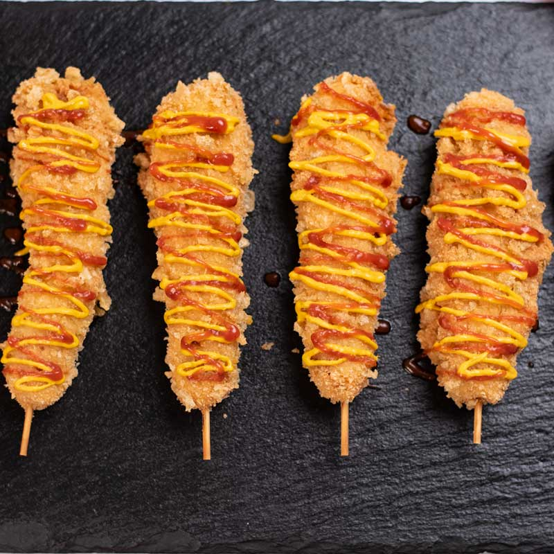 Keto Korean Corn Dogs covered with mustard and ketchup.
