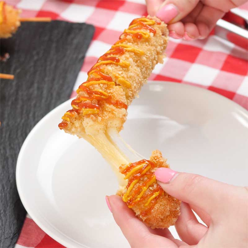A Keto Korean Corn Dog being pulled open to show the melty cheese.