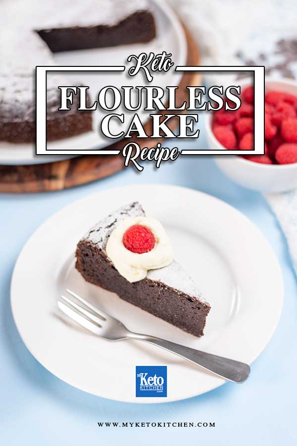 A sliced of Keto Flourless Cake on a plate topped with whipped cream and a raspberry.